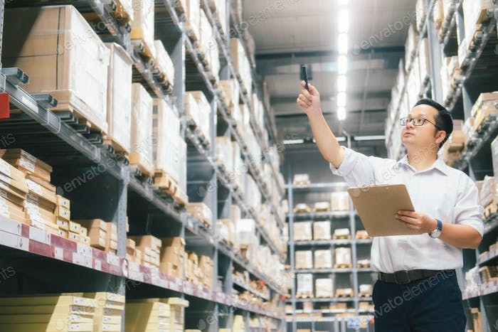 Man warehouse worker checking goods at warehouse.