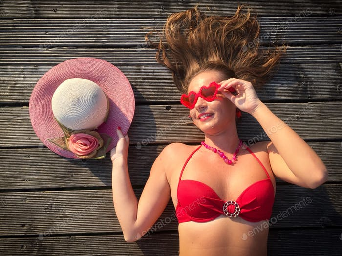 Young woman wearing red bikini and heartshaped sunglasses lying on her back on wooden deck with a