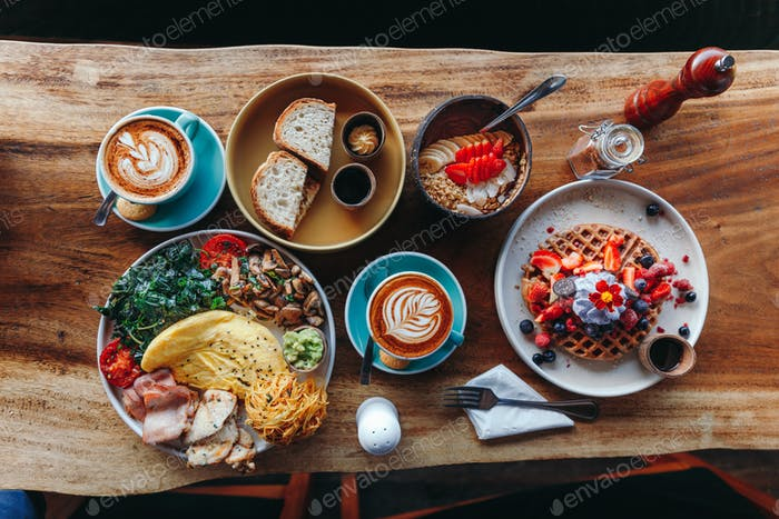 Frühstück am Morgen auf einem Tisch oben, Waffeln mit Sahne, Beeren, Kaffee, Cappuccino, Schüssel, Omlet wit