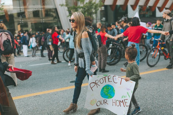 A family at a climate change rally, holding a sign.