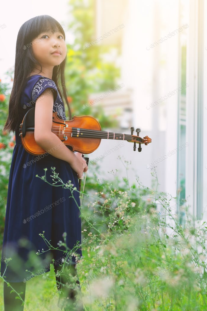 Vertical orientation full body portrait of an Asian little girl with her violin standing in a garden