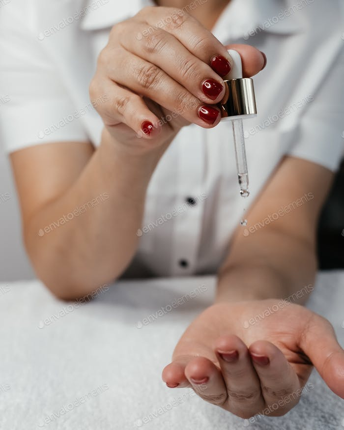 Hands of a woman - a professional beautician and massage therapist with natural cosmetic skin oil