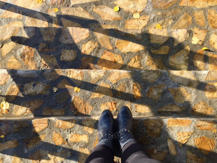 Looking down at woman's black boots standing on the steps with sunlight reflecting on them