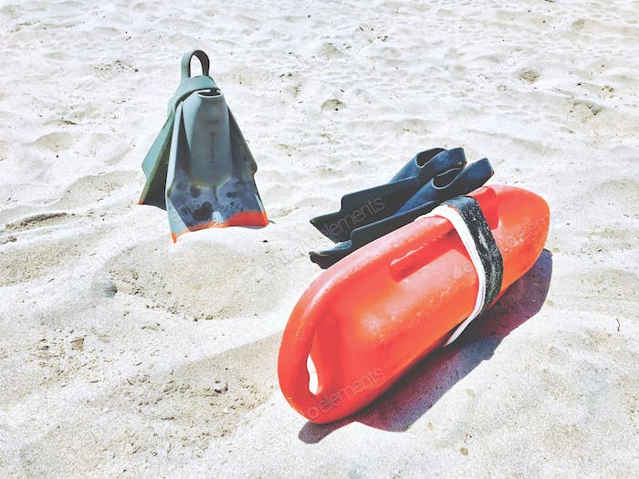 Fins and a floatation device is placed for easy access so that a lifeguard can quickly grab it on