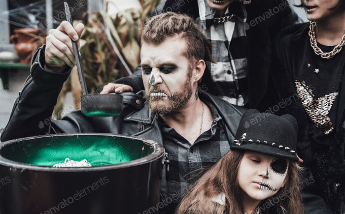 Scary family, mother, father, daughters celebrating halloween. Cauldron of potion.Terrifying black s