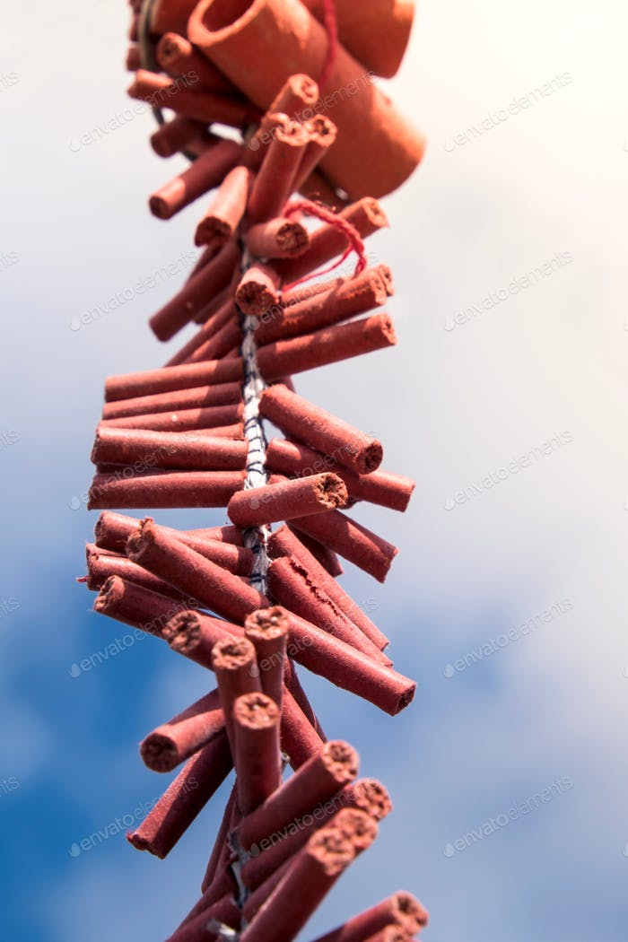 Close-up of Chinese New Year firecrackers against blue sky and clouds