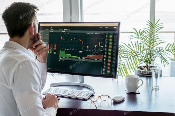 Profesional sentado en el escritorio viendo información de datos en la pantalla del monitor del ordenador.