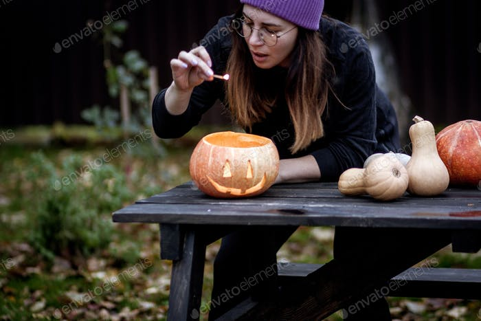 Young woman with pumpkin jack o lantern outdoors