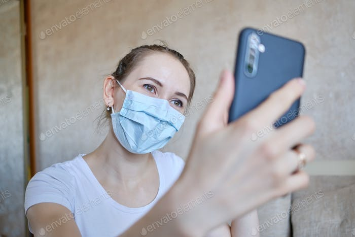 A girl in a medical mask communicates via video chat at home in quarantine in self-isolation.