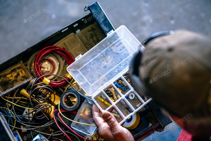 Nahaufnahme einer Person, die während der Reparatur in einem Workshop nach einem Plug in einer Toolbox sucht.