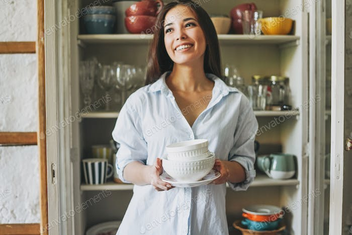 Young smiling asian woman in casual shirt with dishes near vintage sideboard at home