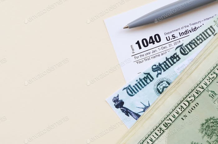 1040 Individual Income tax return form with Refund Check and hundred dollar bills on beige