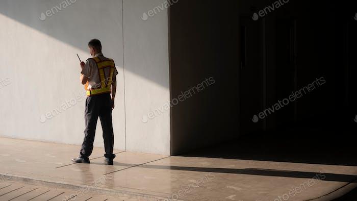 Security guard using walkie talkie while working in underground of parking garage