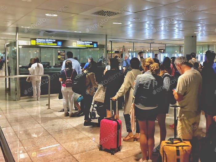Los viajeros hacen cola en aduanas e inmigración en el aeropuerto.