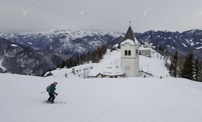 Einsamer Skifahrer fährt bergab in Richtung eines Dorfes auf einem Berg.