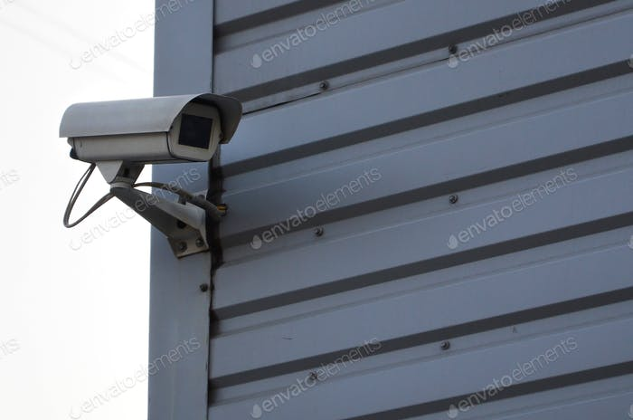White surveillance camera built into the metal wall of the office building