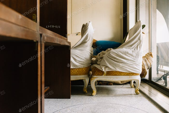 Old chair covered by white clothes