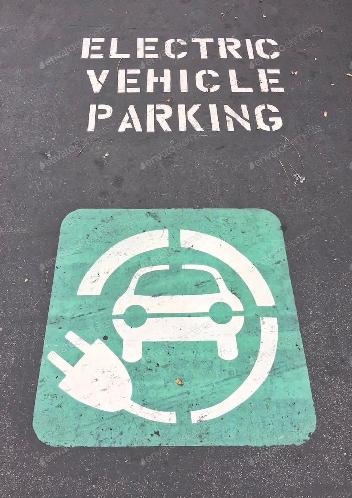 Ausgewiesener Elektrofahrzeugparkplatz mit Wörtern und Symbolen auf dem Boden gemalt