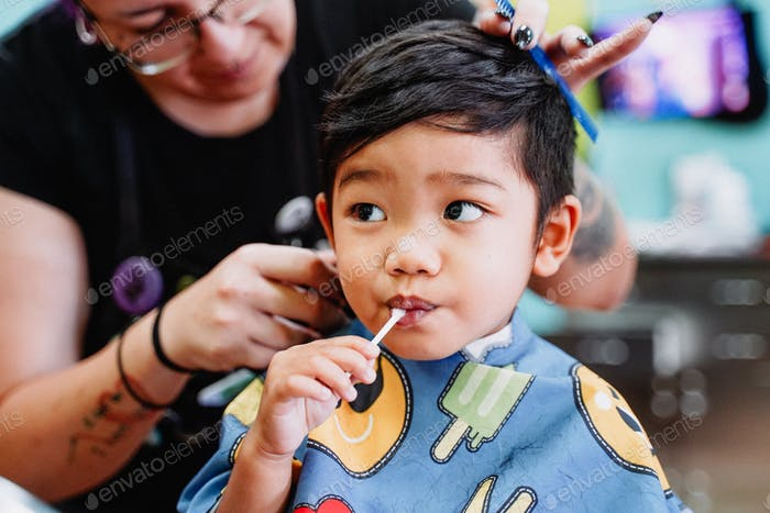 Diverse cute young little boy getting a haircut while eating a lollipop.