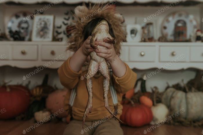 Photograph of a young child in a lion hat holding a frog.
