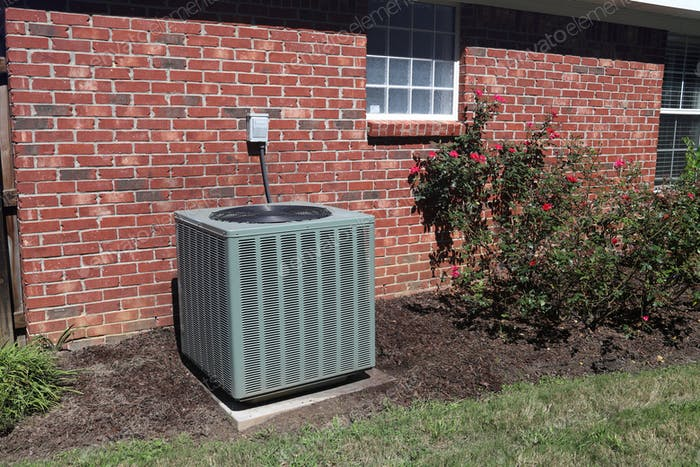 Air conditioner compressor condenser unit outside a brick home, used to cool the house