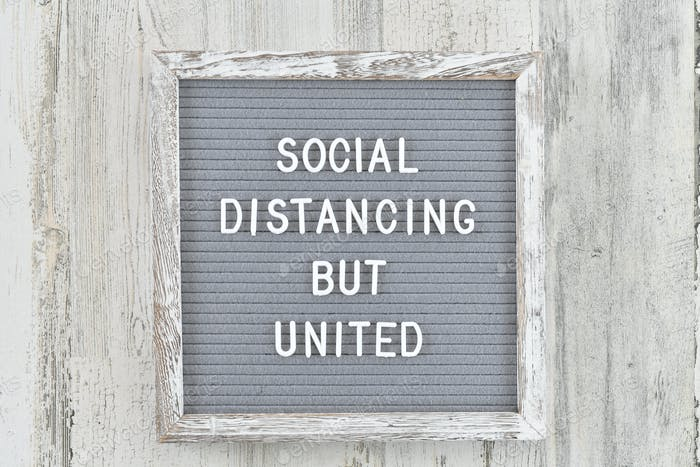 Social Distancing But United - spelled out on a gray white distressed wood message letter board.