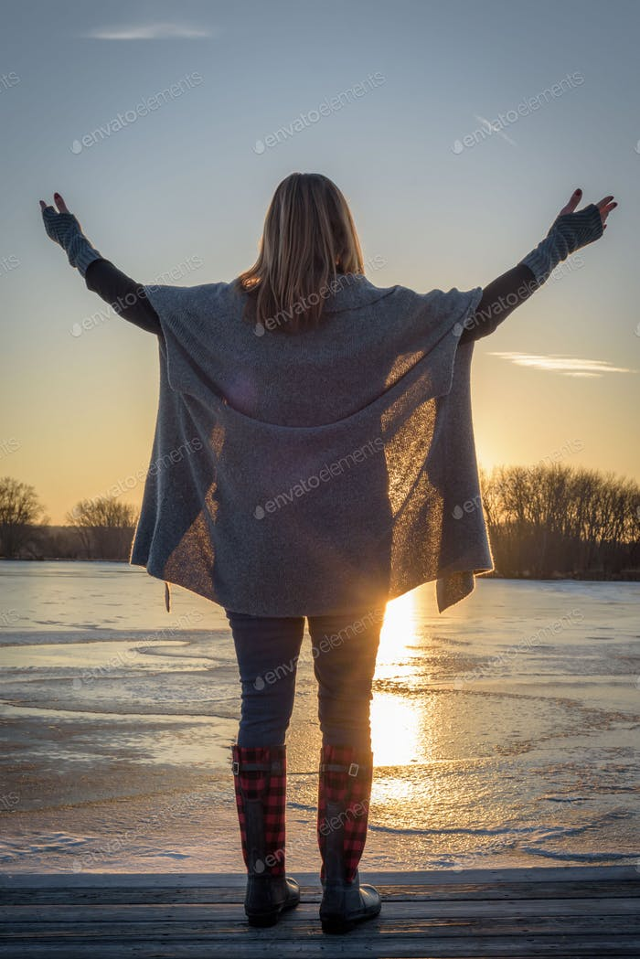 Woman with raised hands admiring sunset