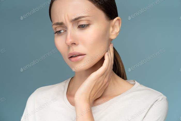Frau überprüft Lymphknoten, erkältet, leidet unter Halsproblemen, isoliert auf Studio Blue