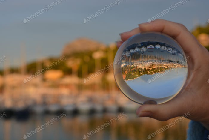 Looking through crystal ball to scenic port with yachts in harbour, Javea, Alicante Province, Spain