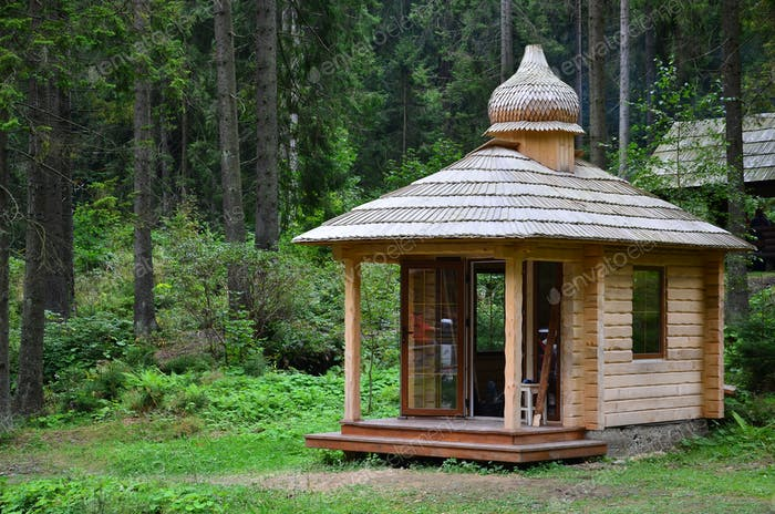 Small natural house, which is built of wood. The building is located in the forest