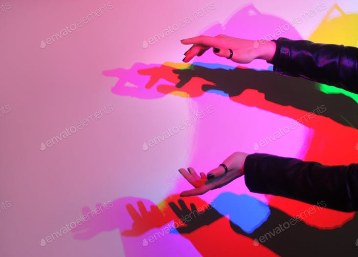 Colorful shadows of hands on the wall