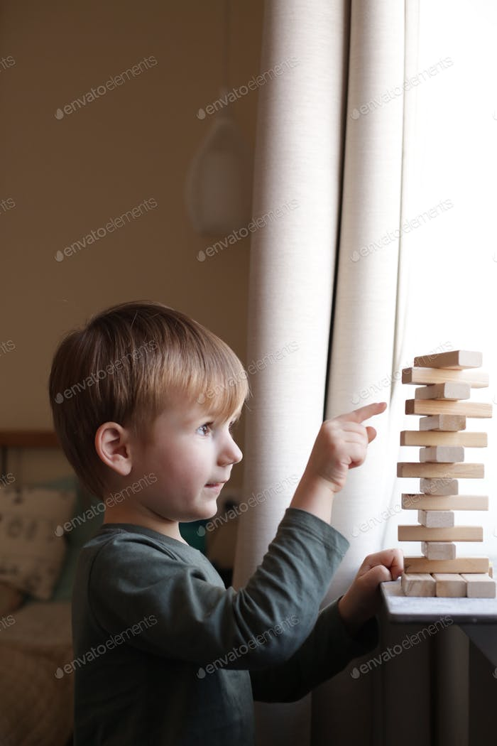 little boy of european appearance playing Jenga at home