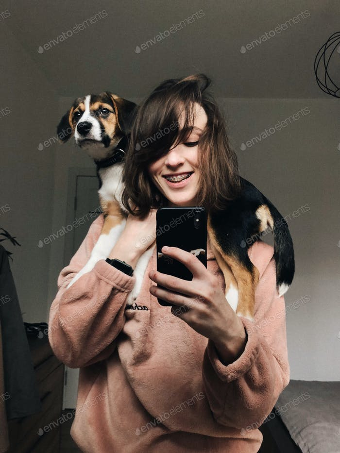smiling girl taking photo with cute doggy