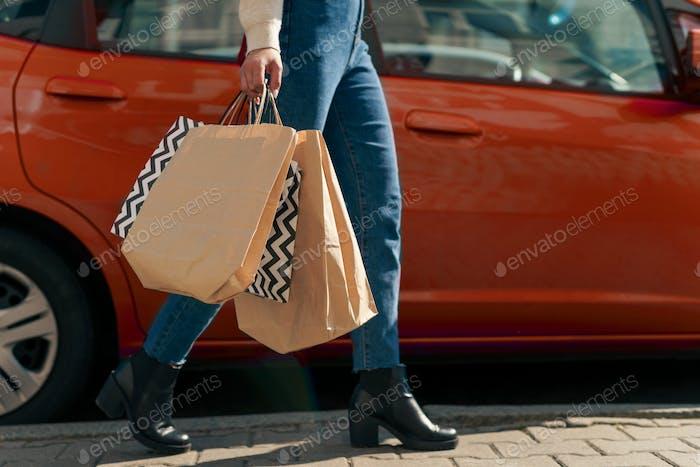 Woman with shopping bags walking past an orange car