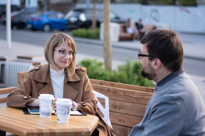 Young man and woman are sitting at a table on the street in the city and discussing their affairs
