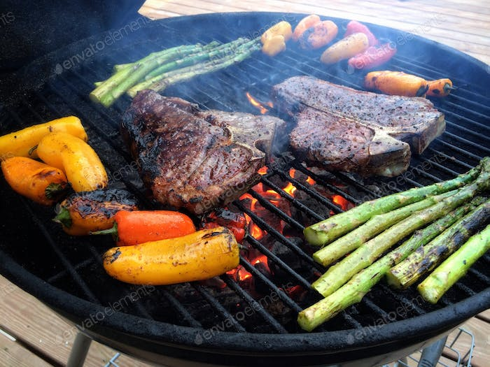A colorful view of steak, sweet peppers, and asparagus atop a black charcoal grill.