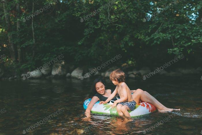 Eine Mutter und ein Sohn im Sommer im Schlauch am Fluss.