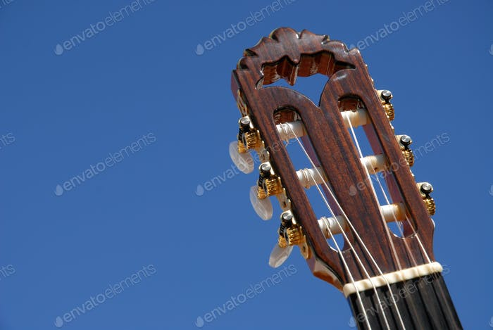 Classical guitar, headstock and tuning pegs against blue sky with copy space