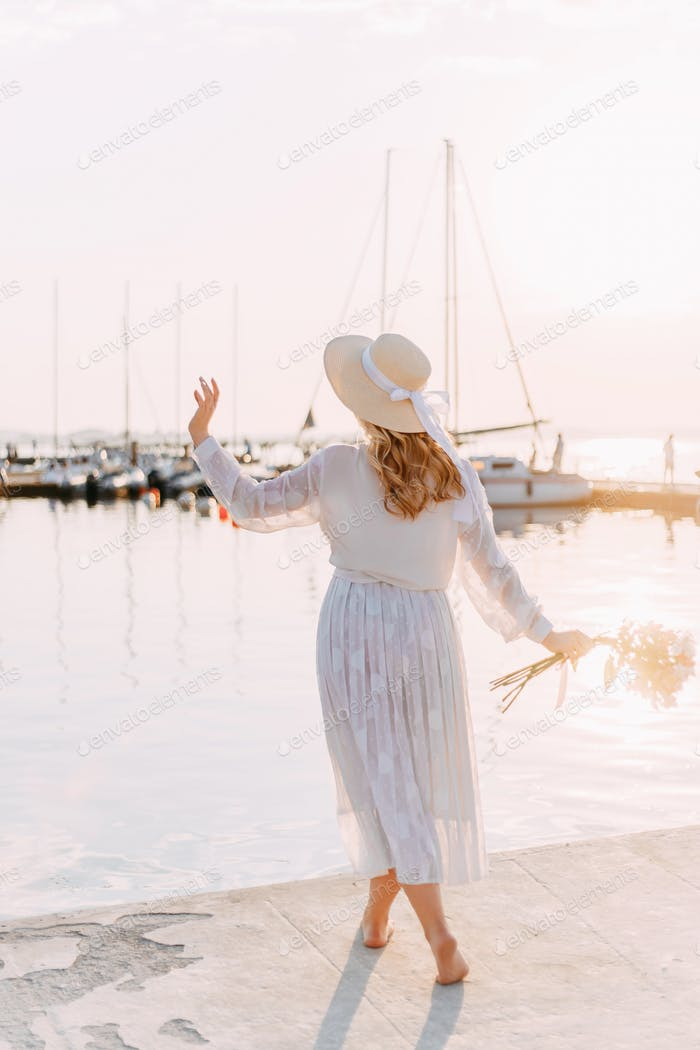 Beautiful cute elegant lady girl relaxing at the pier on the beach by the boats yachts in the summer