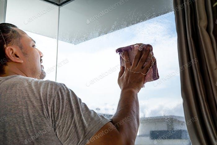 El concepto de limpieza de apartamentos en casa. Un hombre en la ventana y se limpia con un trapo.