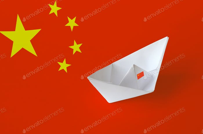 China flag depicted on paper origami ship closeup. Oriental handmade arts concept