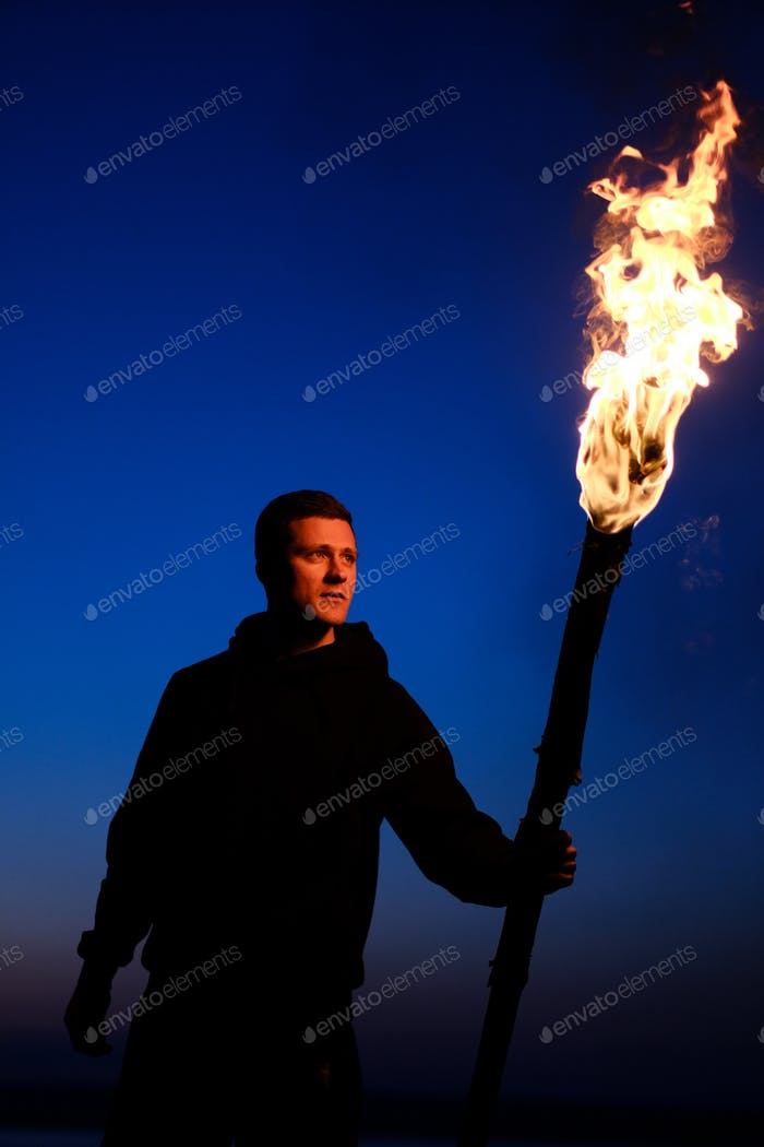 Male, man holds torch with featuring fire and looking for it. Exploration and expedition concept.