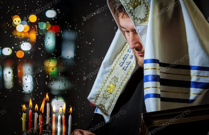 Jewish Religion holiday symbol for lights man hand lighting candles in menorah for Hanukkah