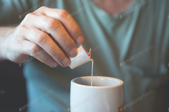 man putting creamer into coffee