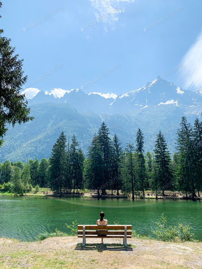 A girl sitting on a bench looking at the river and the mountains on the background