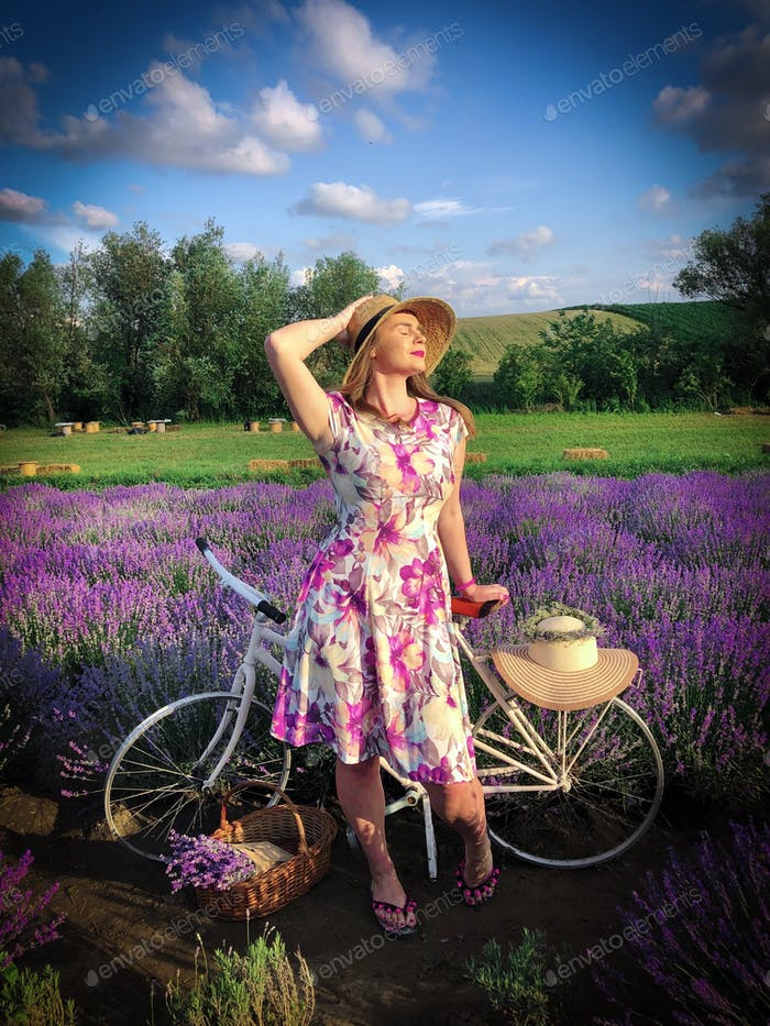 Woman in summer dress standing near a bicycle in a field of lavender