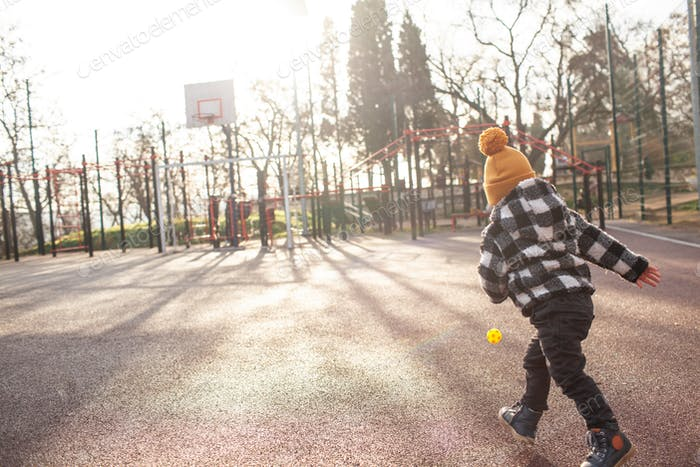 Back view of two years old kid playing in kids playground with little ball