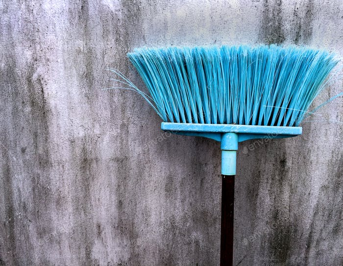 Old Cyan Plastic Broomstick for Cleaning Wet Floor Against Dirty Wall