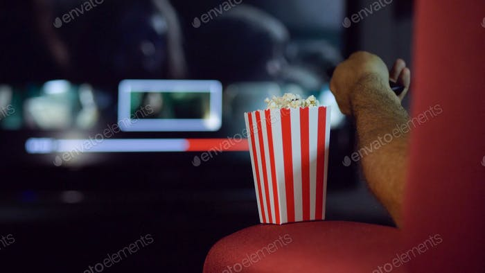 Eating popcorn while watching a movie on the couch at home.