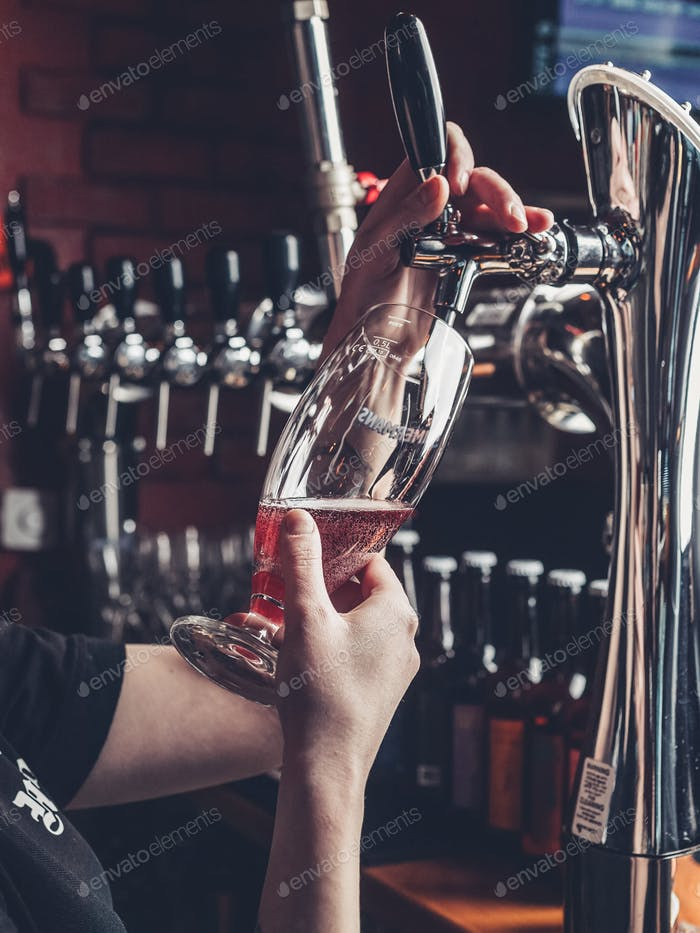 Bartender pours beer into a glass. pint, pouring, nightlife,